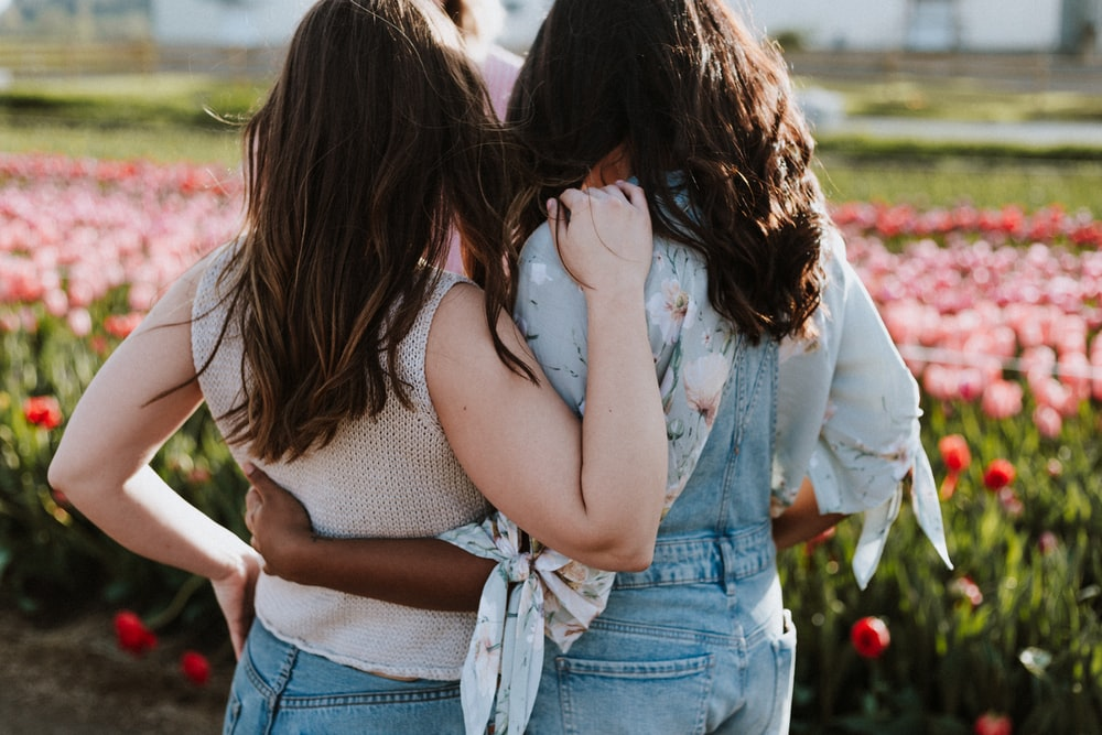 two women in front of flowers