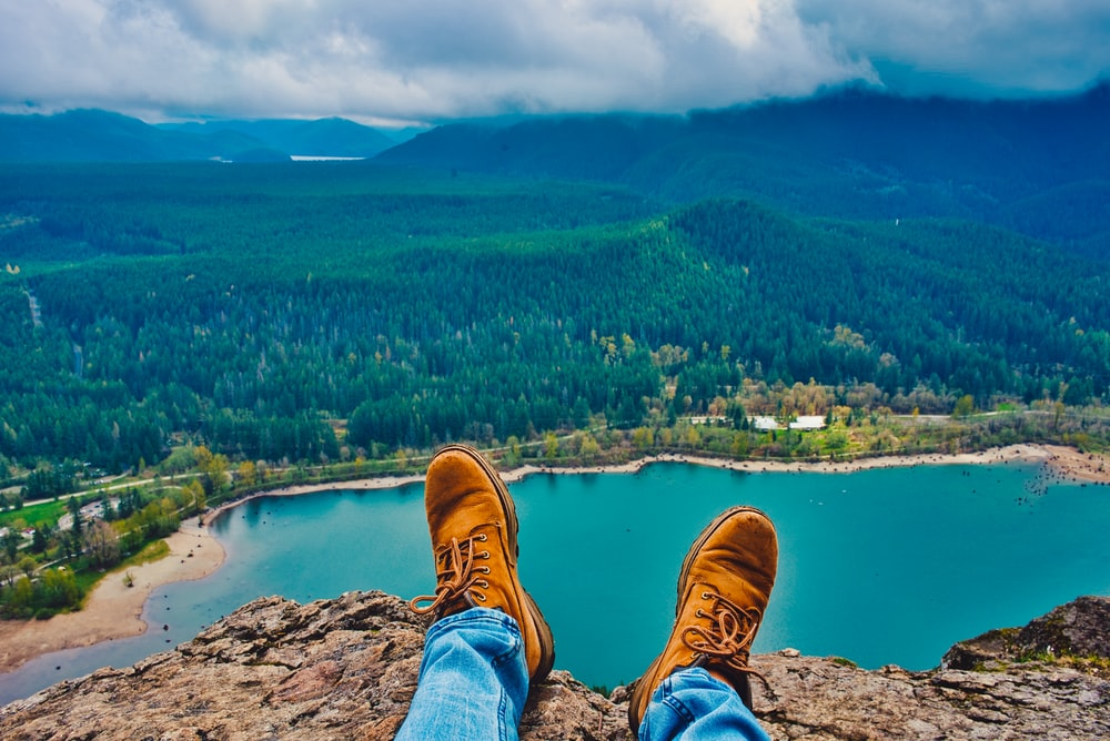 man sitting on cliff overlooking city