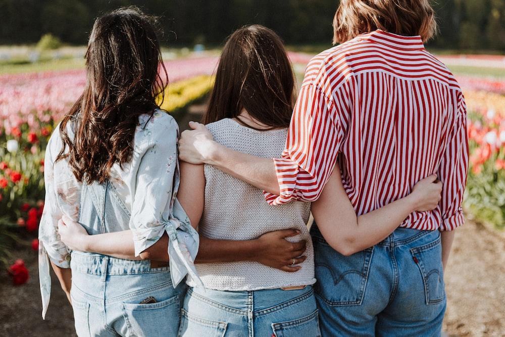three women holding hand in front of flower garden