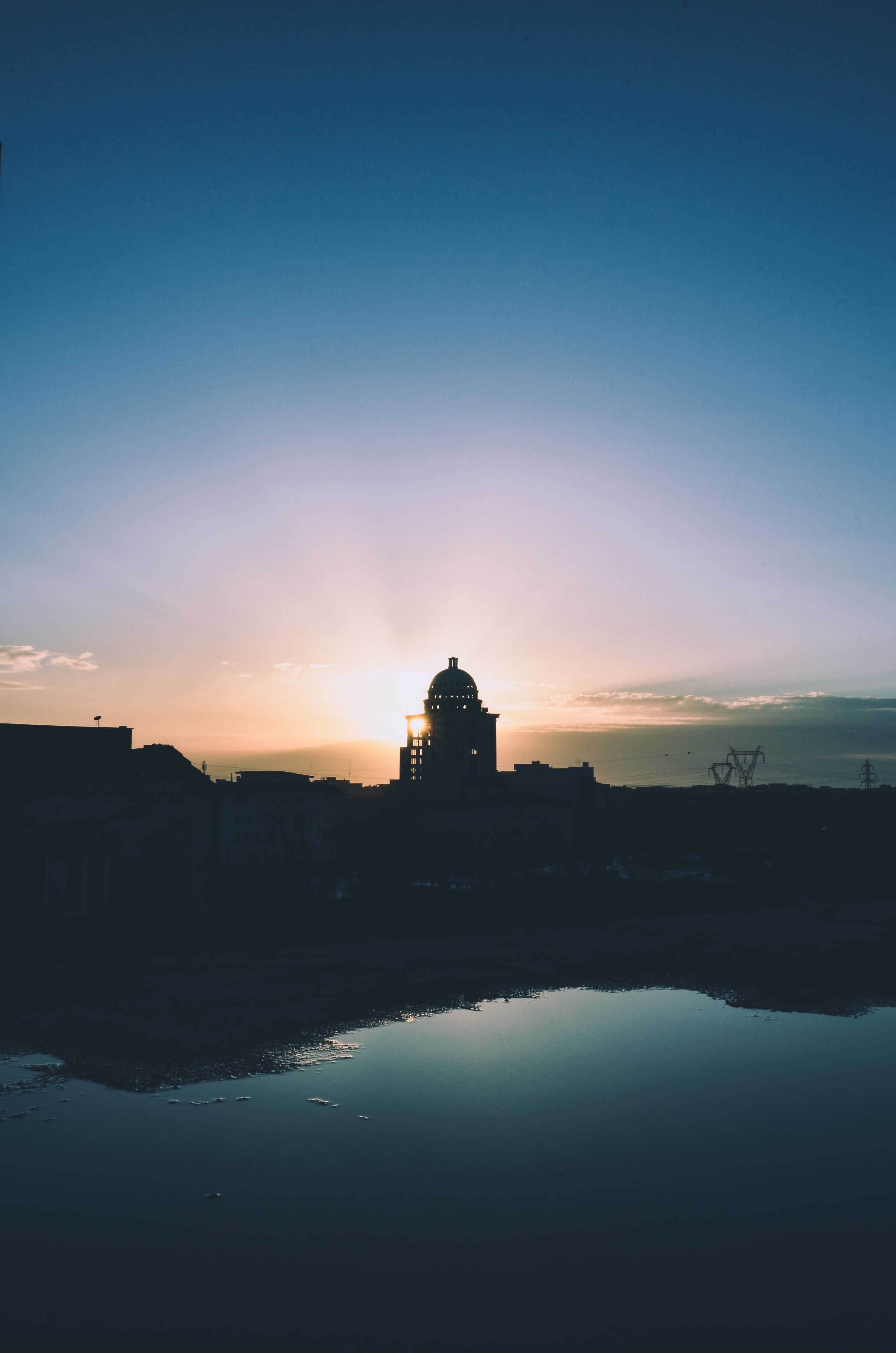 silhouette photography of building near body of water