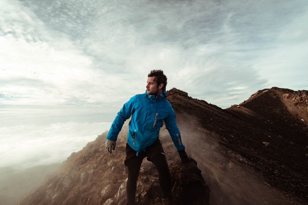 man in blue jacket standing on cliff