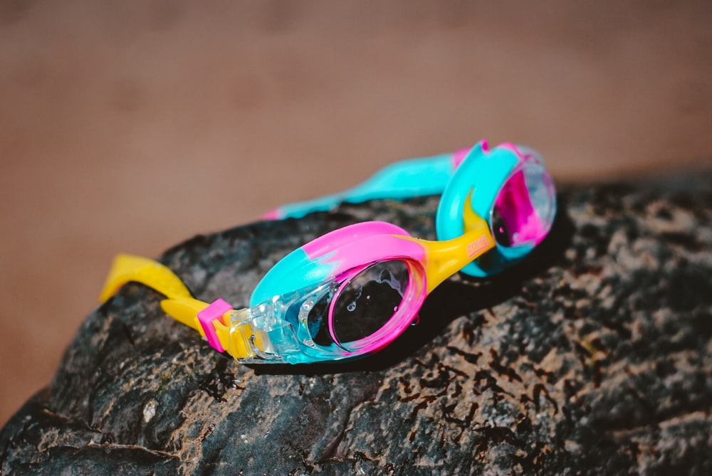 teal and pink goggles on brown boulder