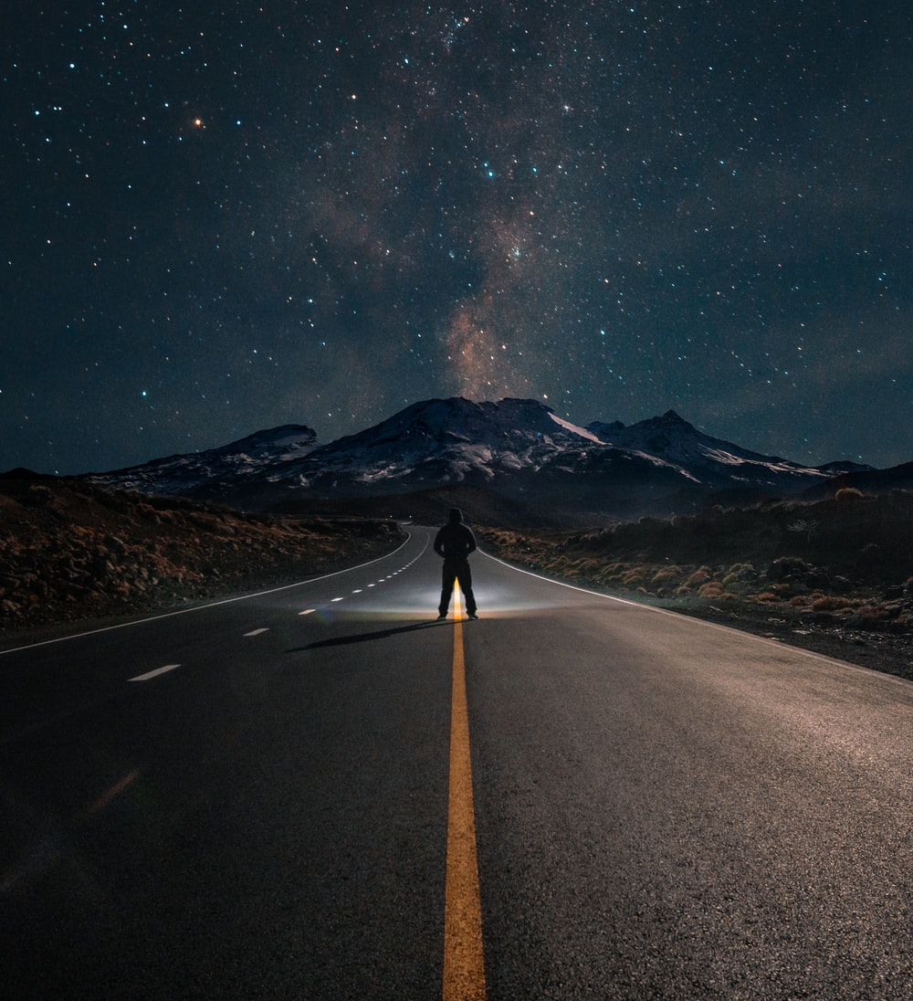person standing at road during night time