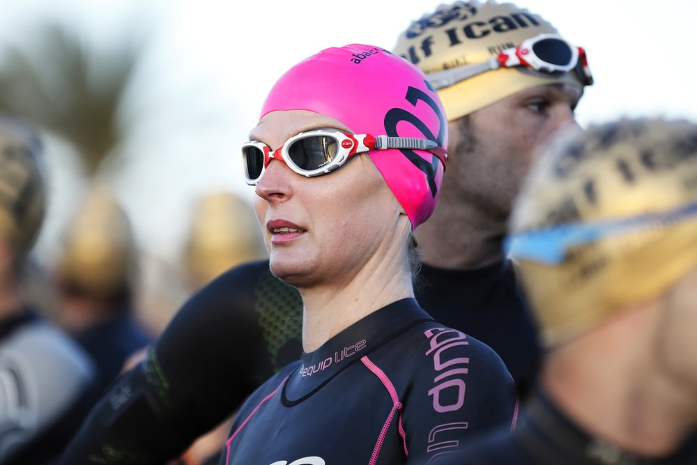 selective focus photography of woman wearing swimming cap