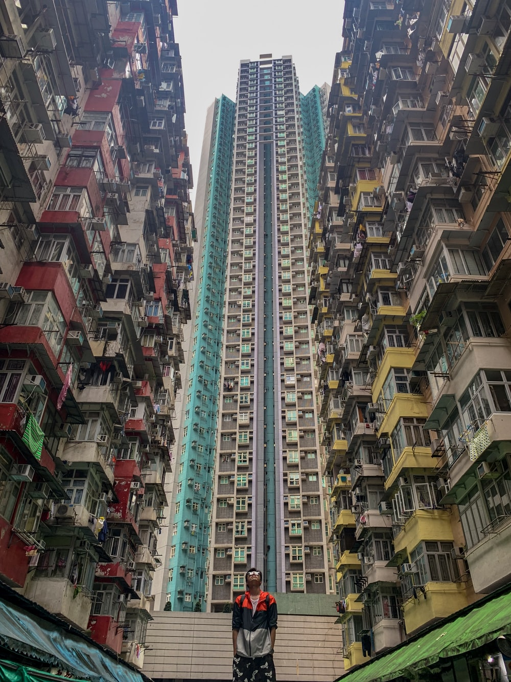 man standing in between of high-rise buildings