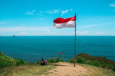 red and white flag beside beach indonesia zoom background