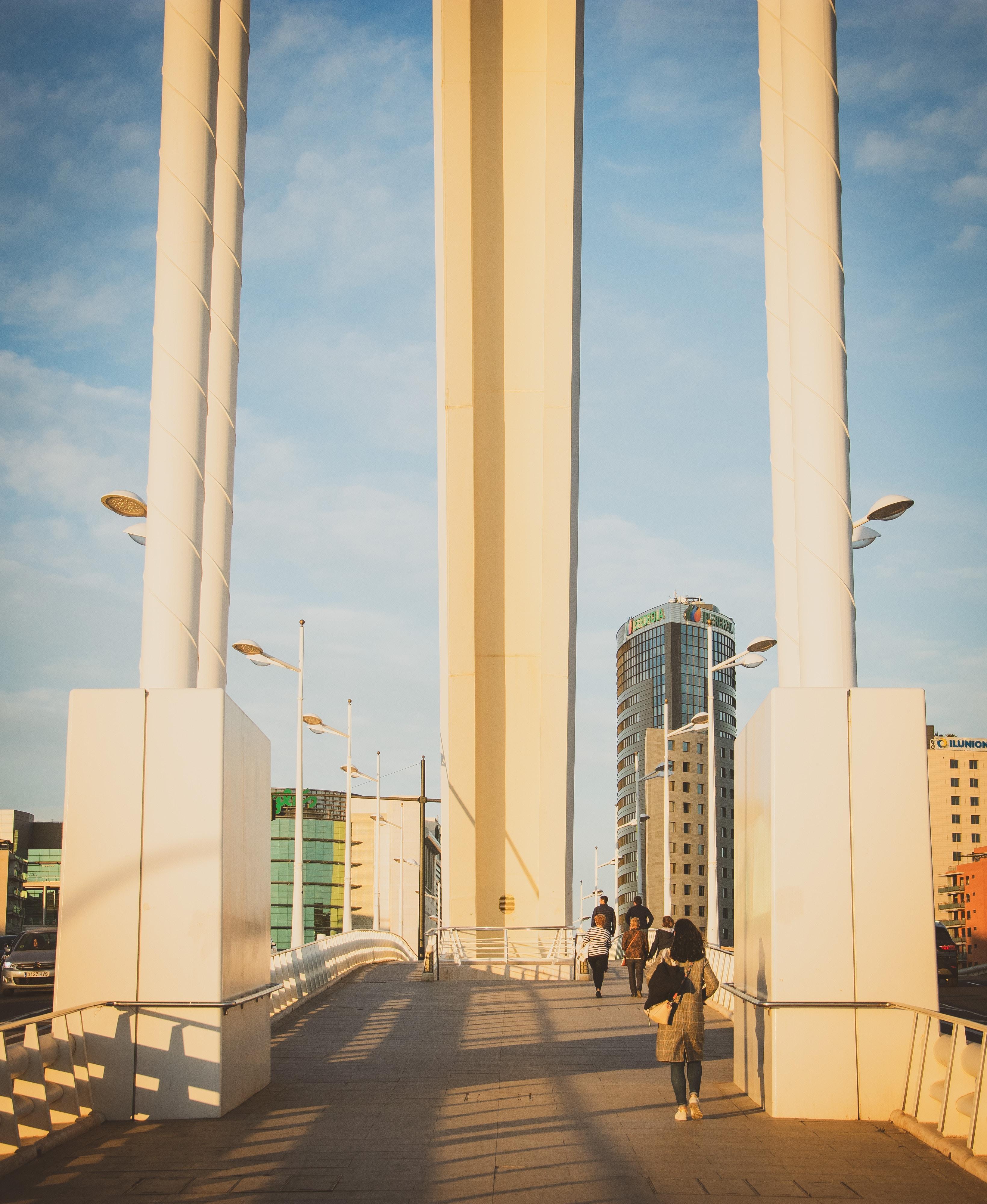 people walking on bridge near buildings during daytime