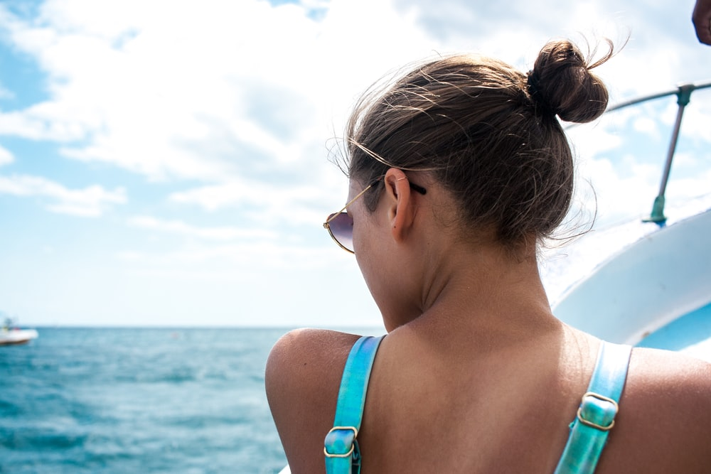 woman wearing teal top on white boat during daytime