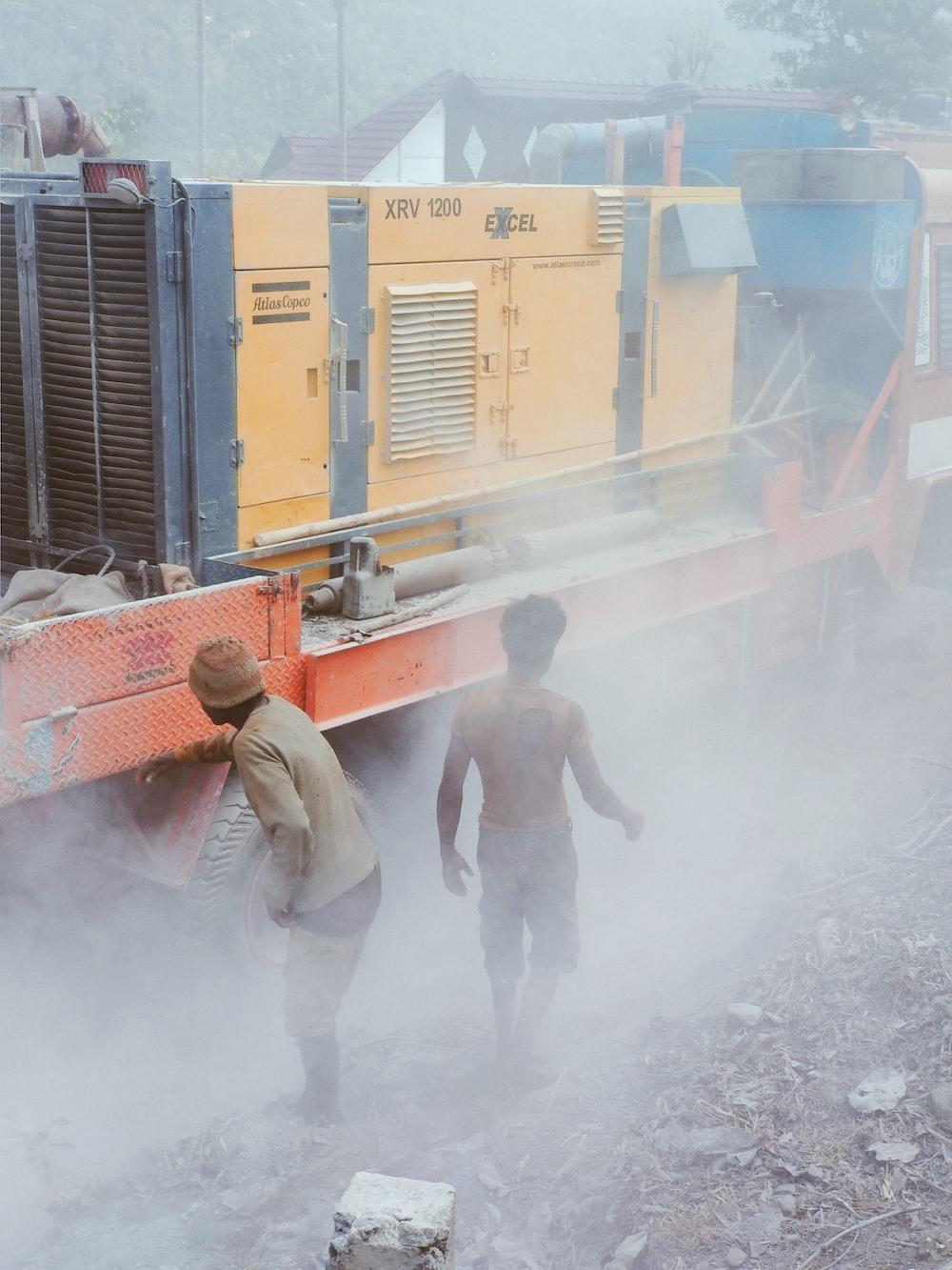 two men standing near diesel generator