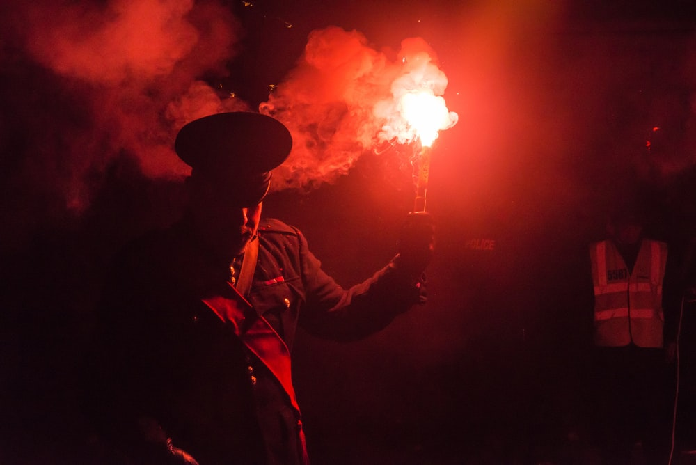 person holding red smoke stick