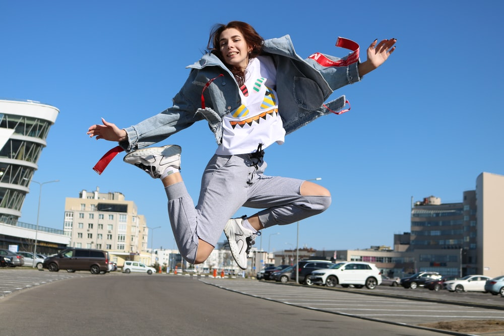 woman wearing blue denim jacket and distressed blue denim jeans jumping during daytime