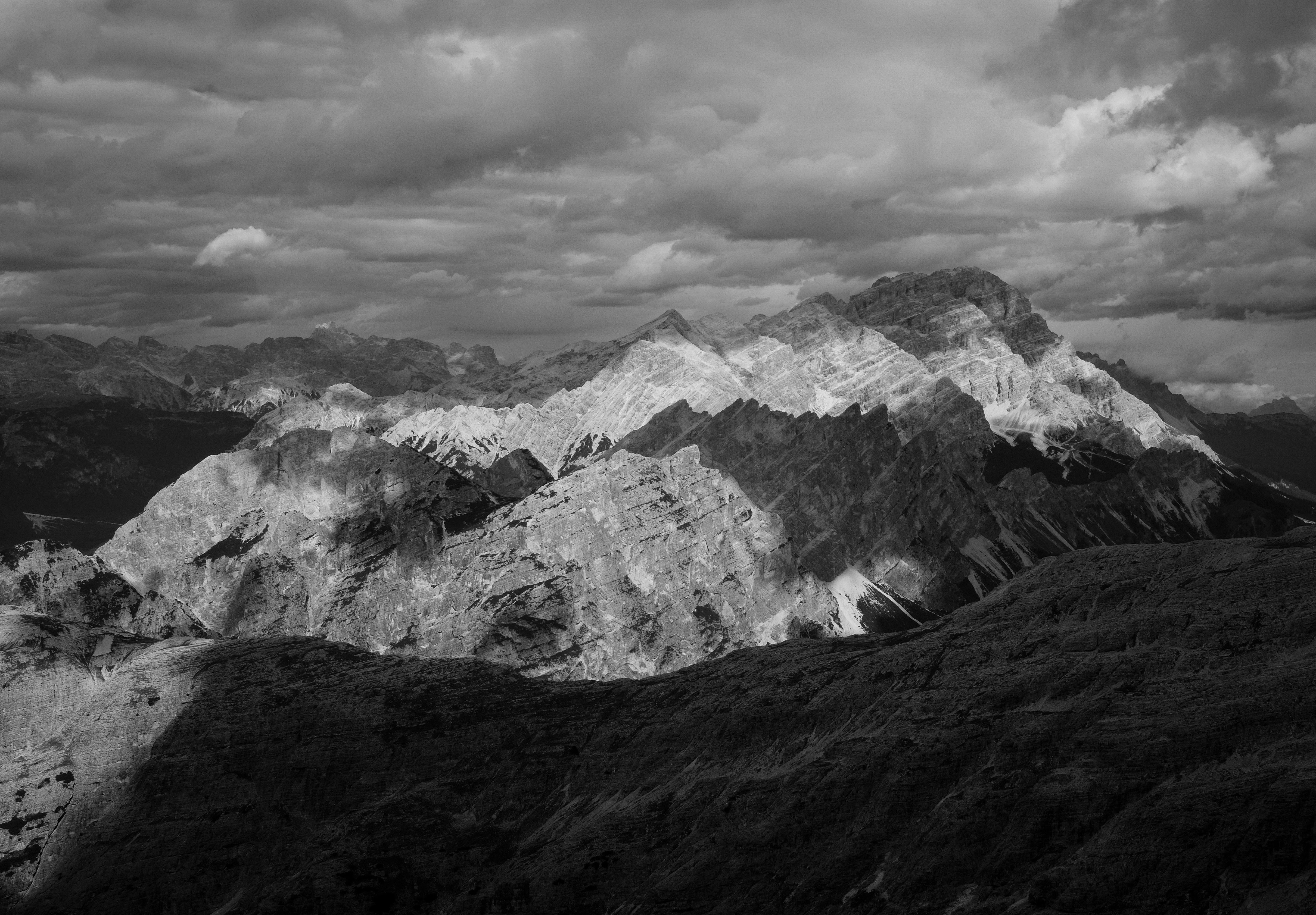 grayscale photo of terrain under cloudy sky