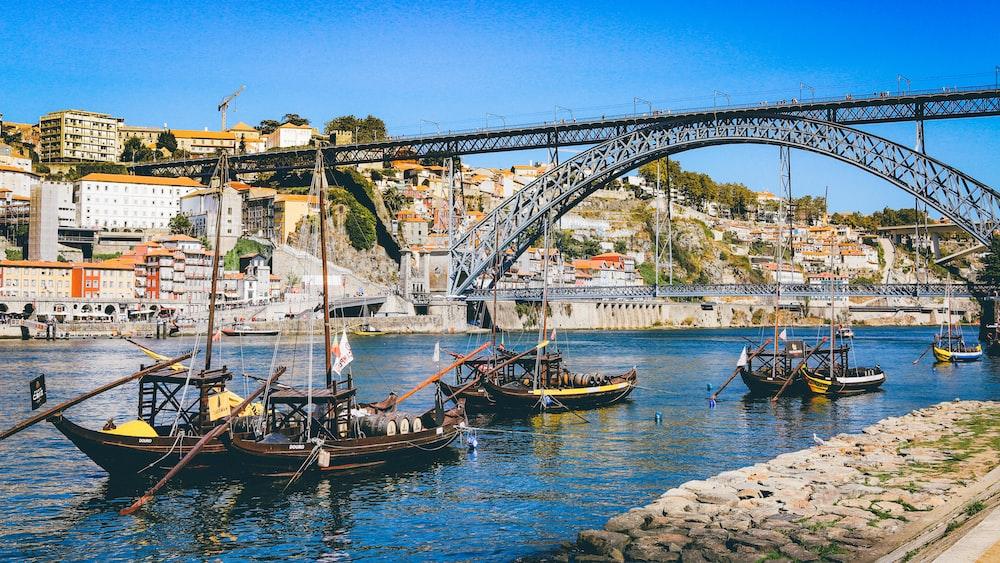 boat sailing near bridge