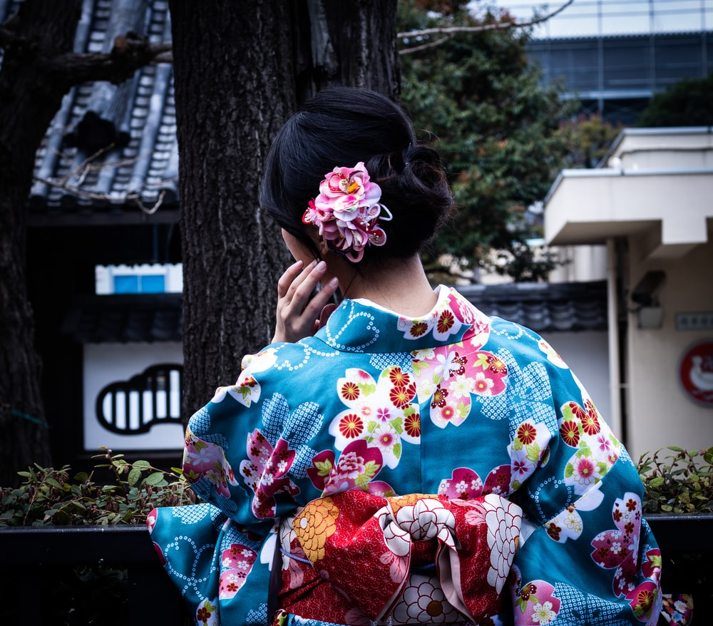 woman wearing blue and multicolored floral kimuno standing and facing near tree