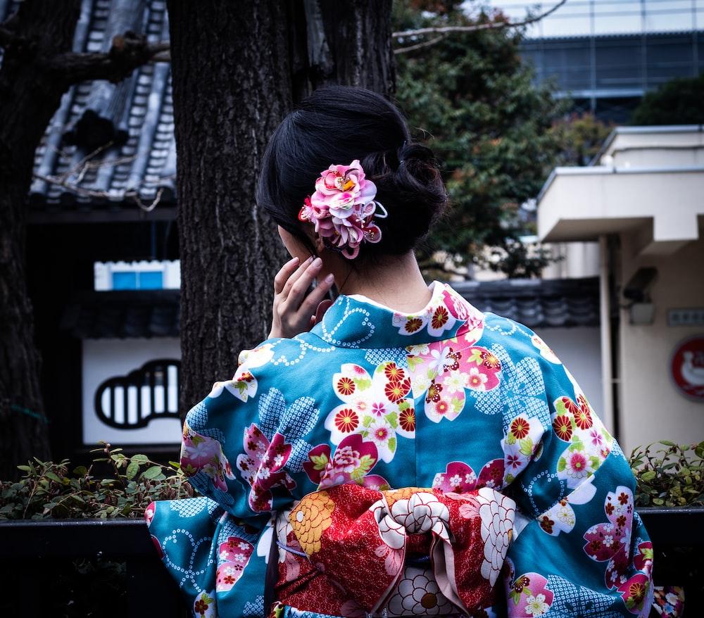 立っていると木の近くに直面している青と色とりどりの花キムノを着ている女性