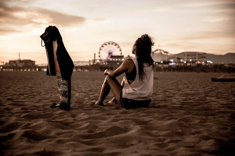 woman sitting on sandy ground