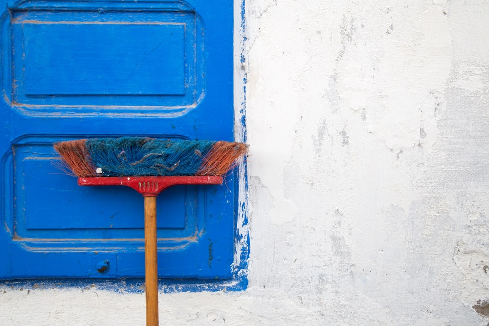 red and orange push boroom leaned on blue door