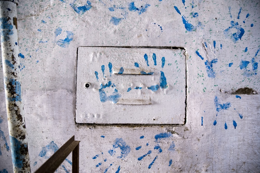 blue hand print on concrete wall