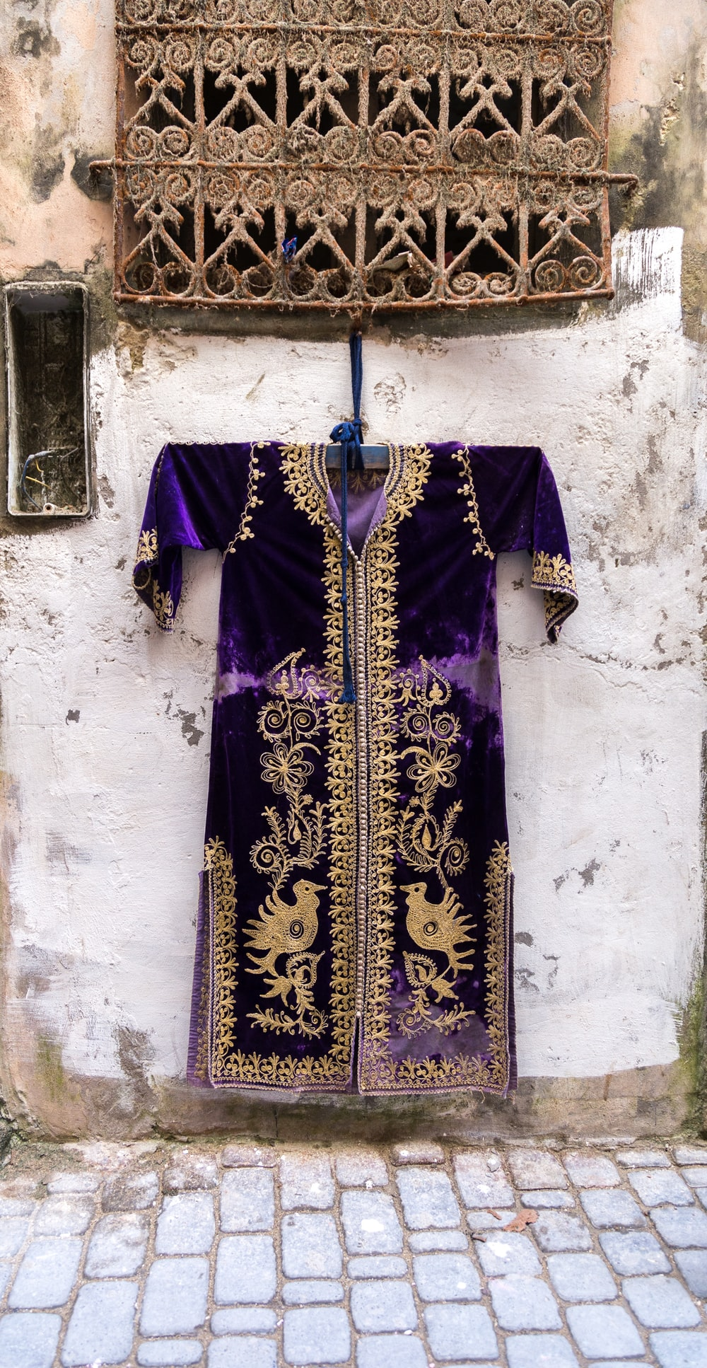 purple and gold long-sleeved dashiki dress hanging by a window