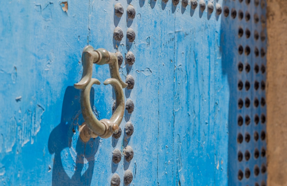 grey door knocker on blue wooden door with rivets