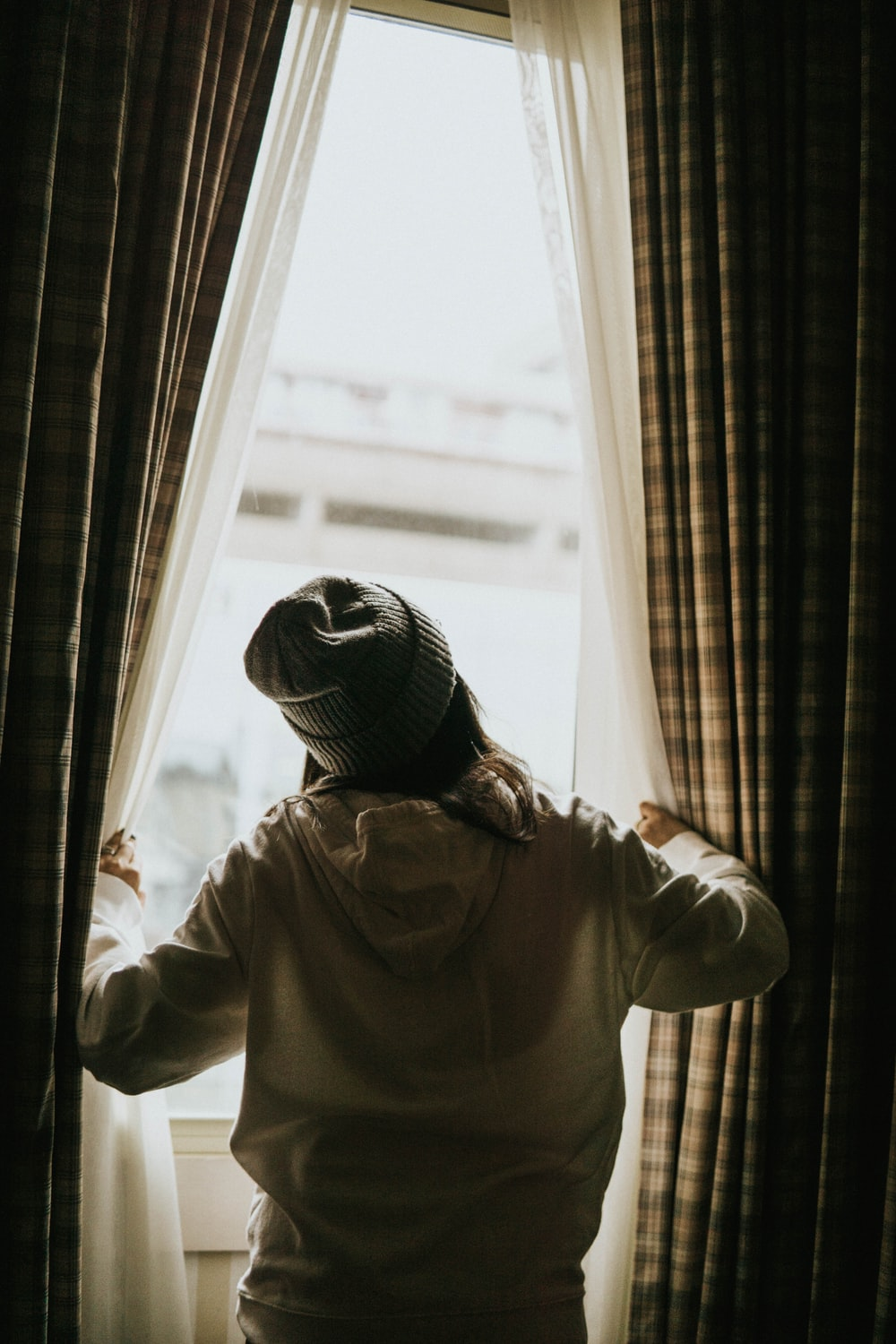 woman in white hoodie starring by the window