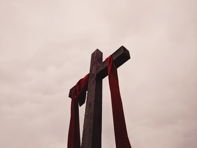 low angle view of cross with red garment christian teams background