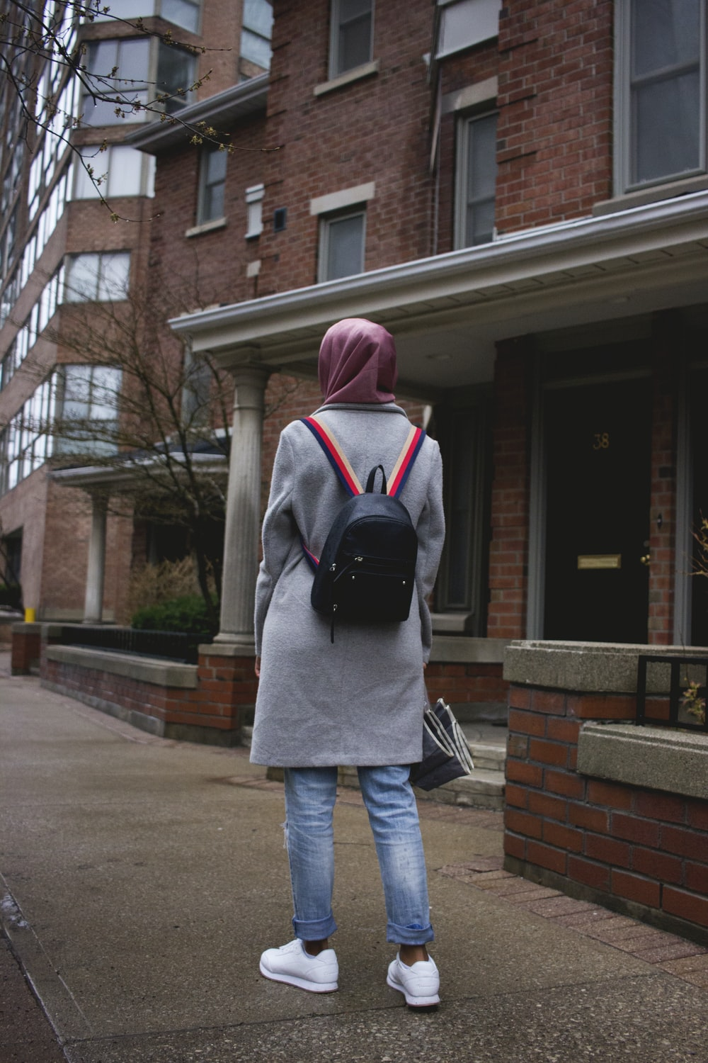 woman in pink hijab headdress, gray coat, blue jeans, white shoes, and black backpack standing near house