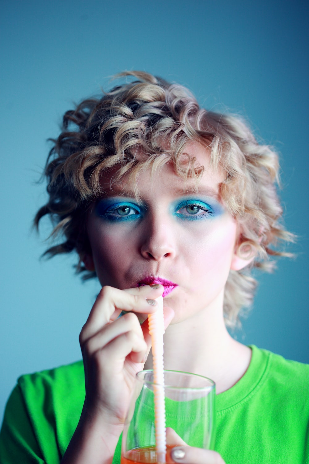 woman with blue eyemake up sipping beverage