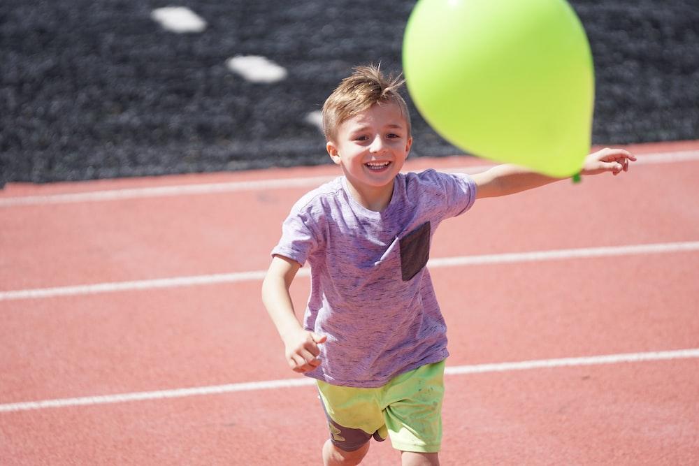 boy in purple shirt chasing green balloon on track field