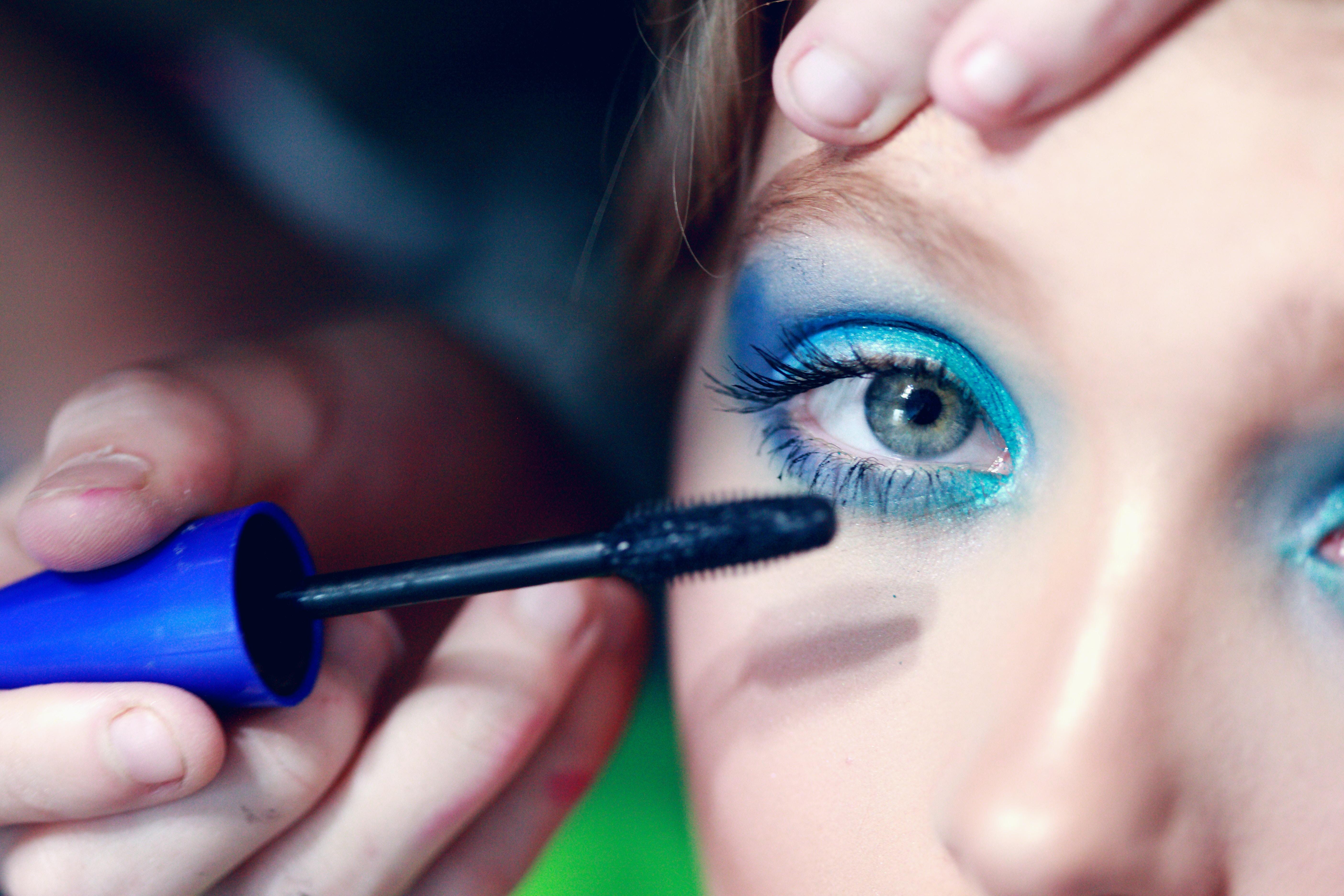 mascara being applied on woman's eyelash with blue eyeshadow