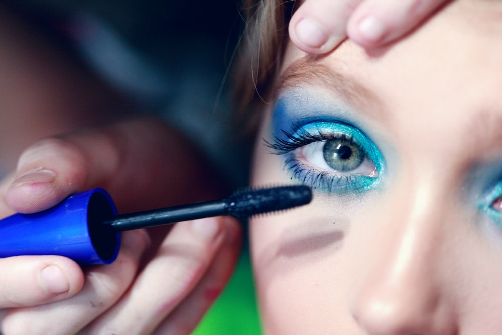 mascara being applied on woman's eyelash with blue eyeshadow