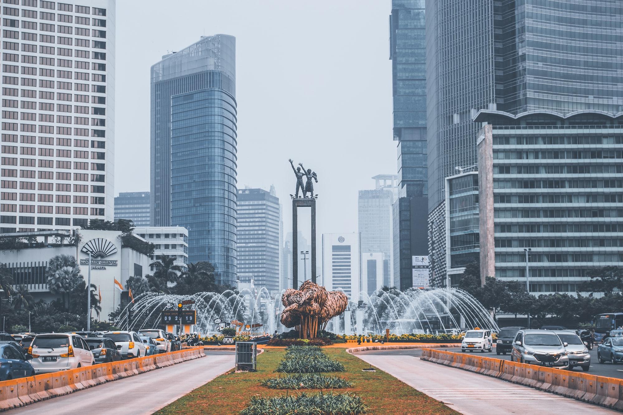 crowded traffic around welcoming statue