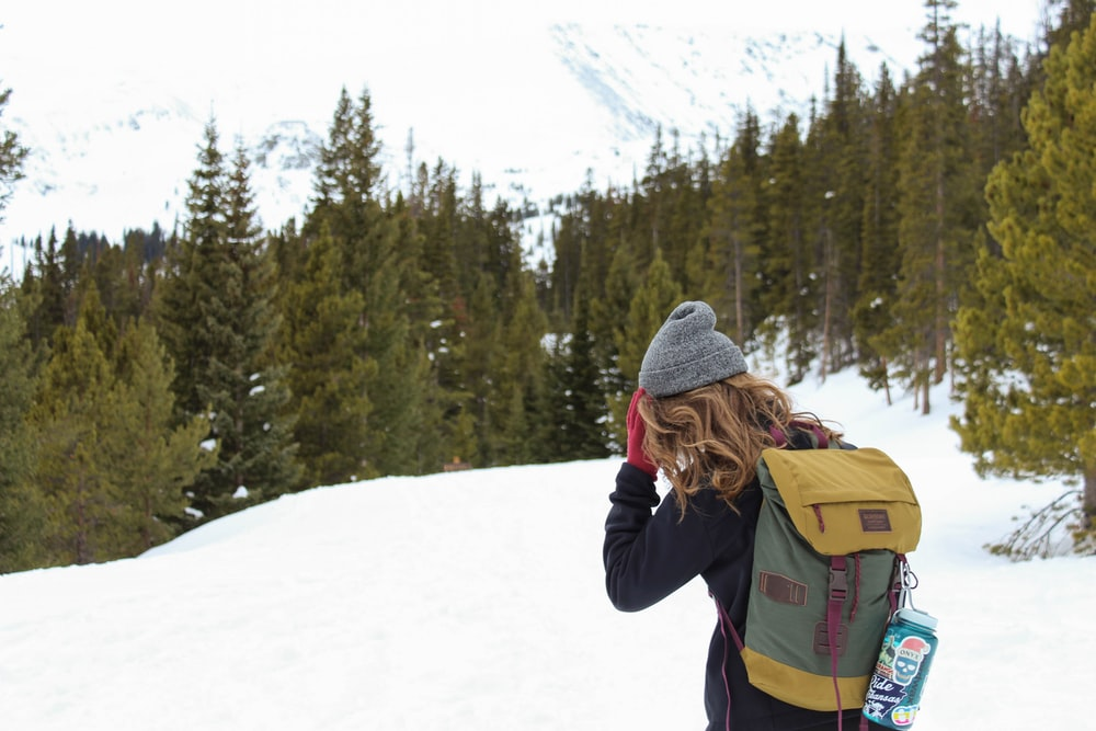 woman wearing black sweater carrying yellow backpack standing on snow