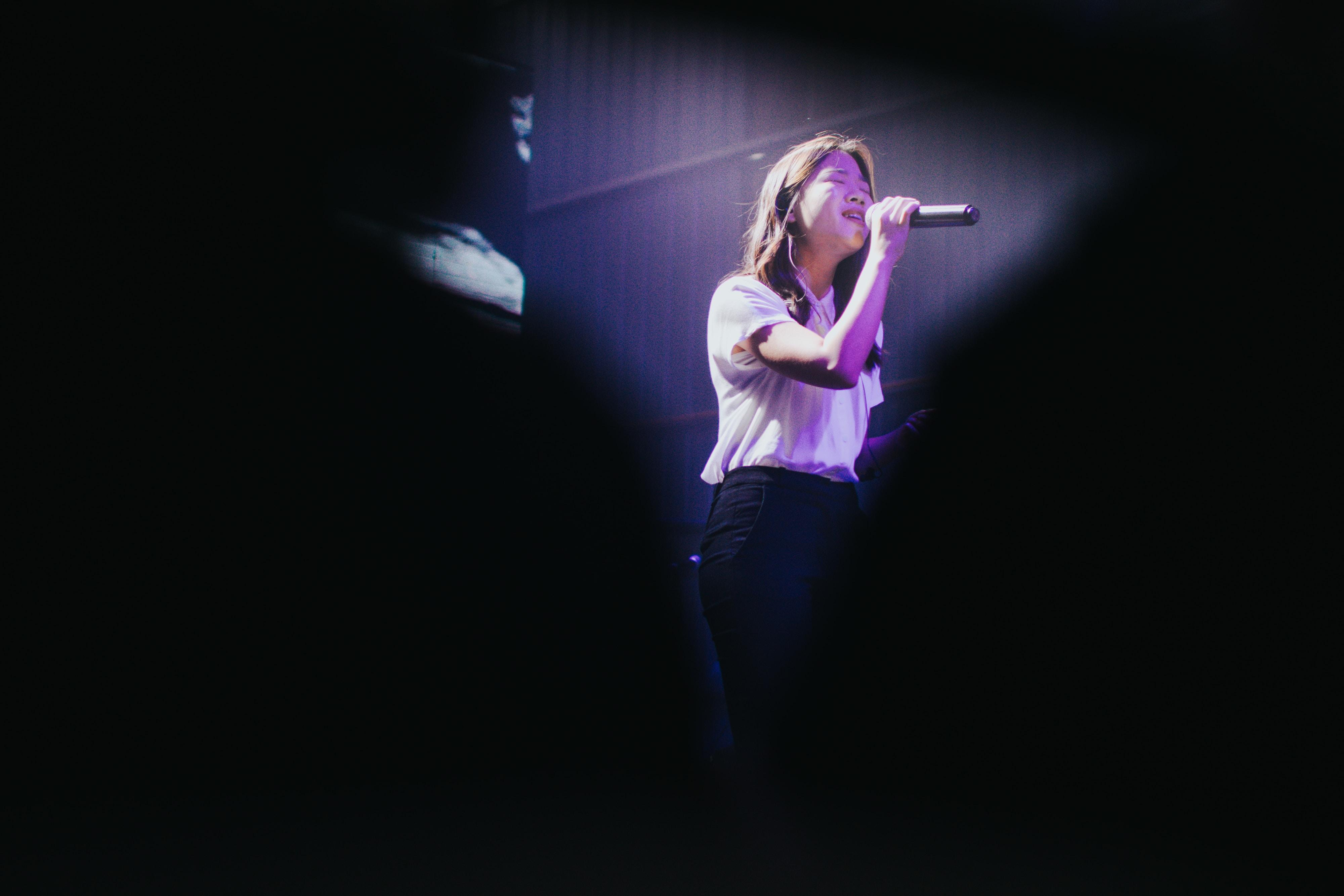woman wearing white shirt singing inside room