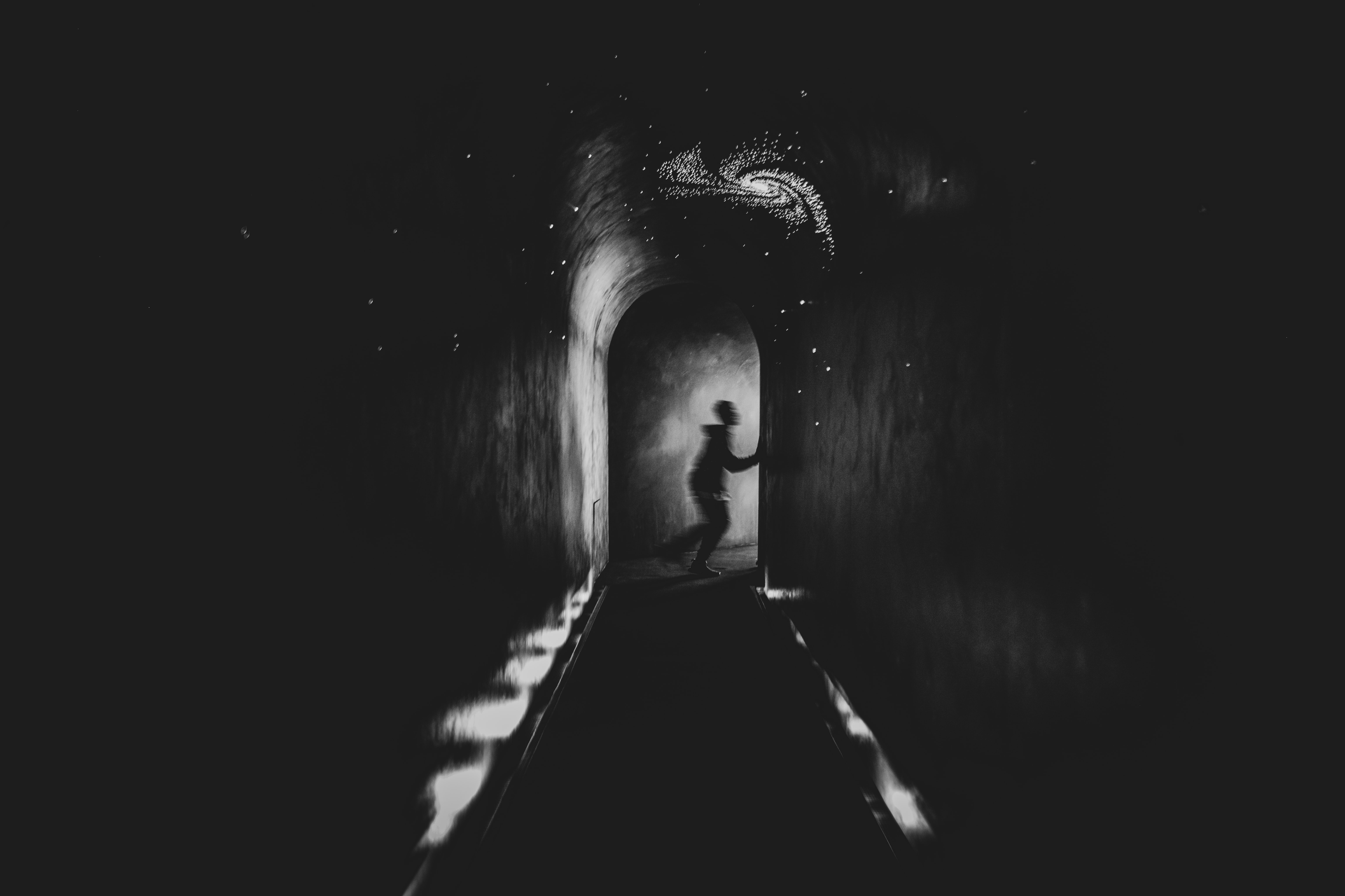 grayscale photo of boy running in hallway