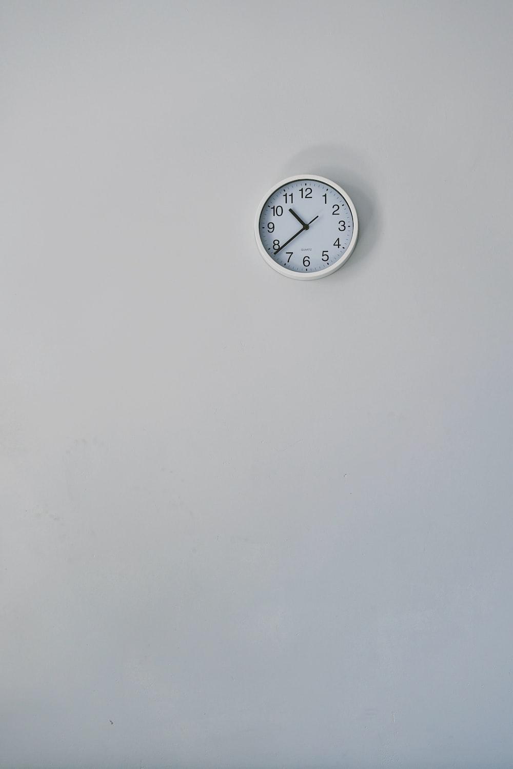 round white analog wall clock displaying 10:38