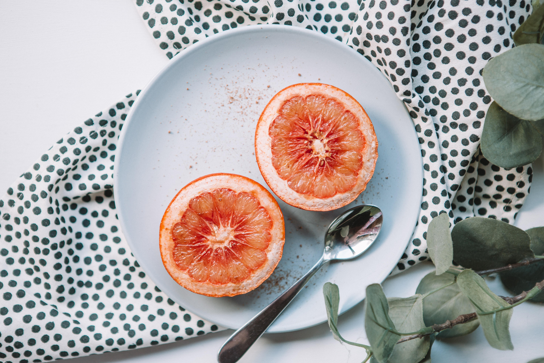 sliced orange on plate near spoon