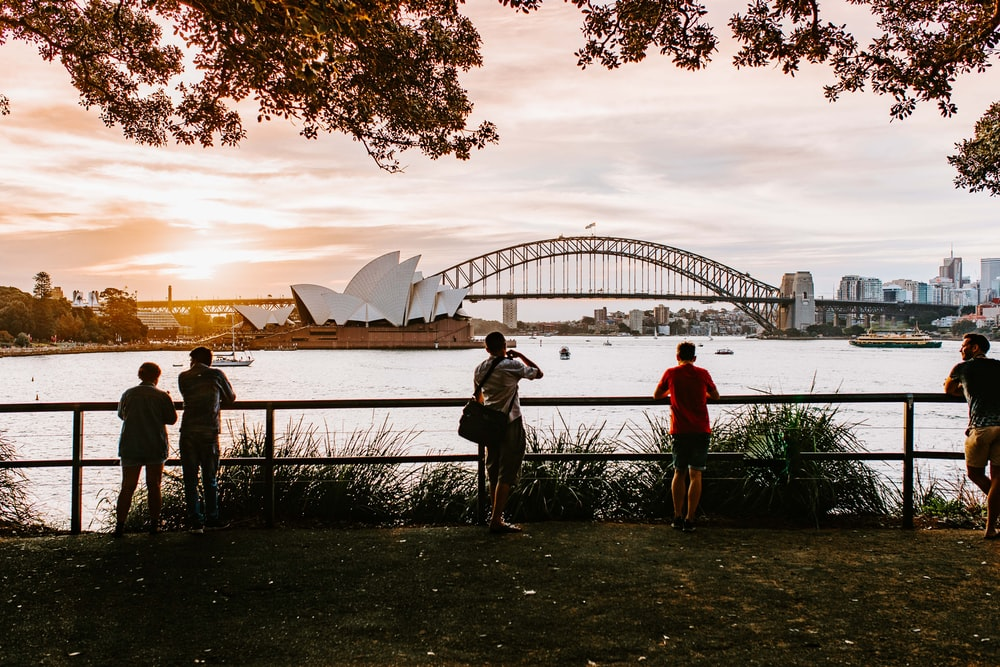 five people standing beside fence with Sydney Opera House in background