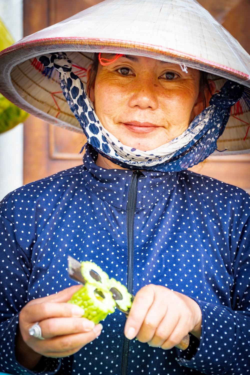 woman in white hat and blue top slicing vegetable
