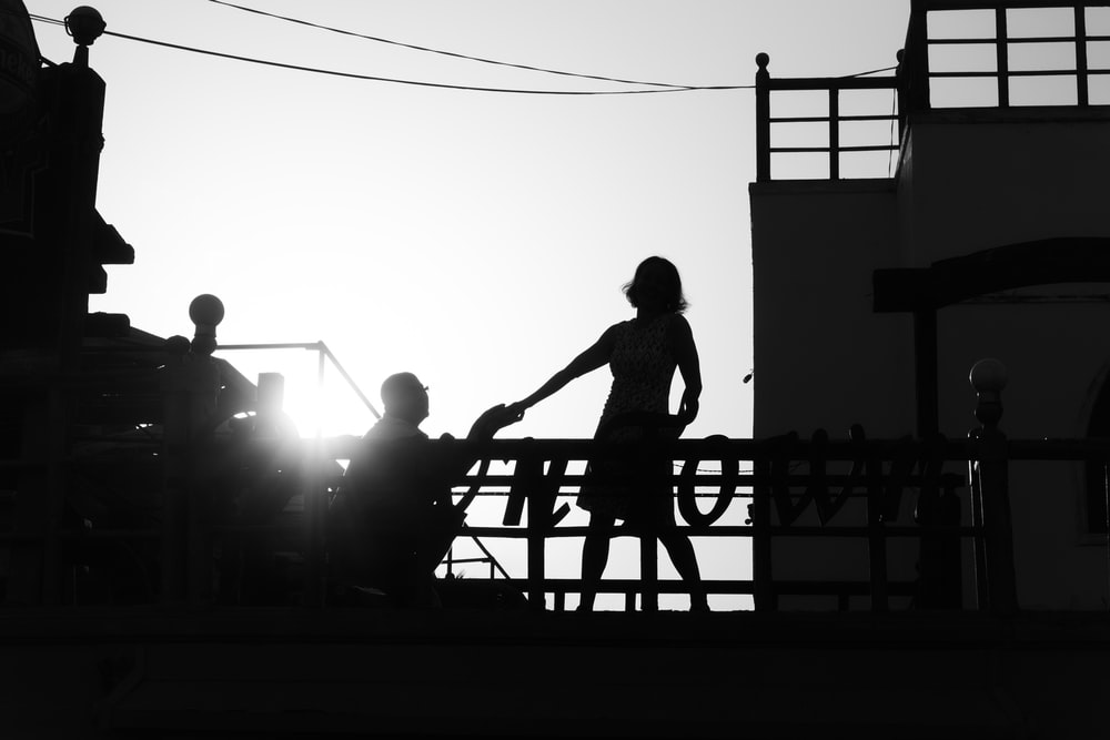 silhouette of girl standing near man kneeling beside railing