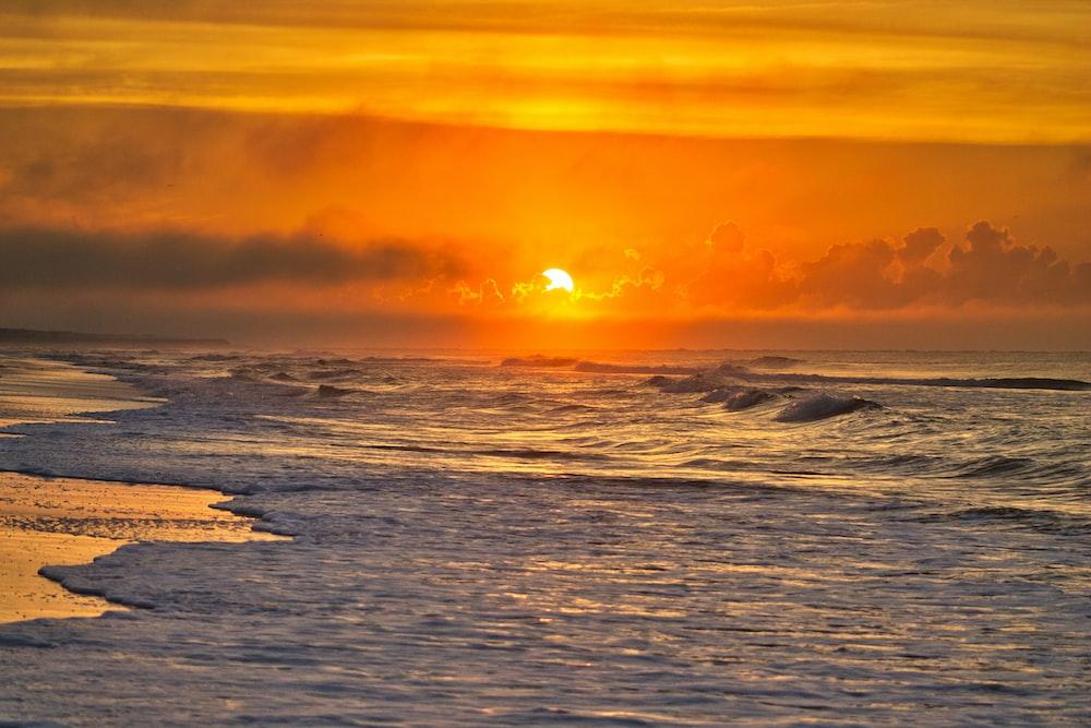 sea waves crashing on shore under sunset