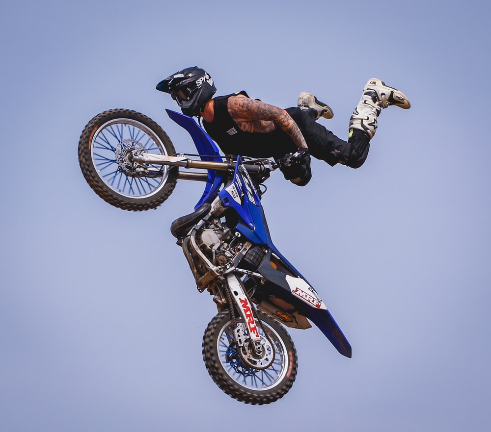 rider with blue dirt bike soaring on air