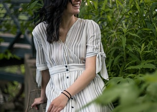smiling woman wearing white and grey striped dress