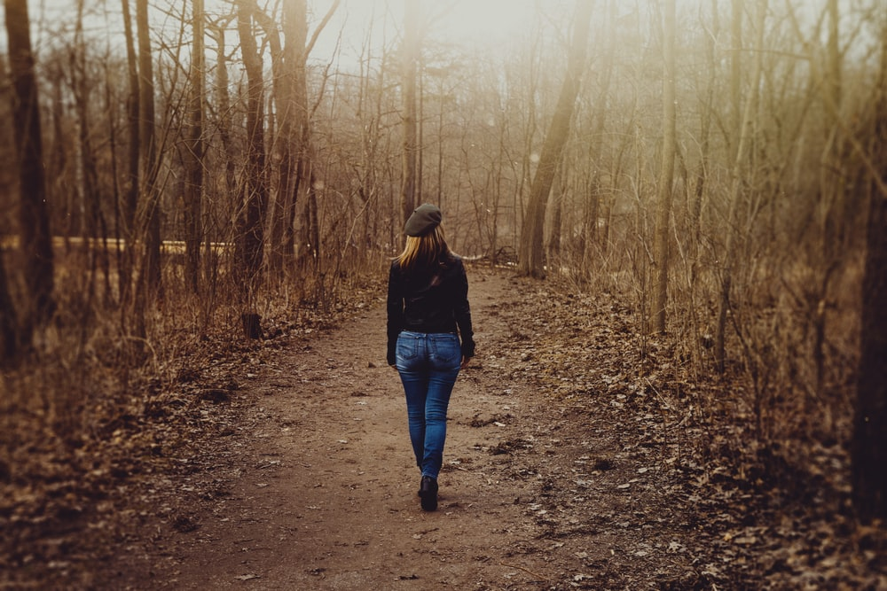 woman in black sweater and blue denim skinny jeans walks on dirt road beside leafless trees