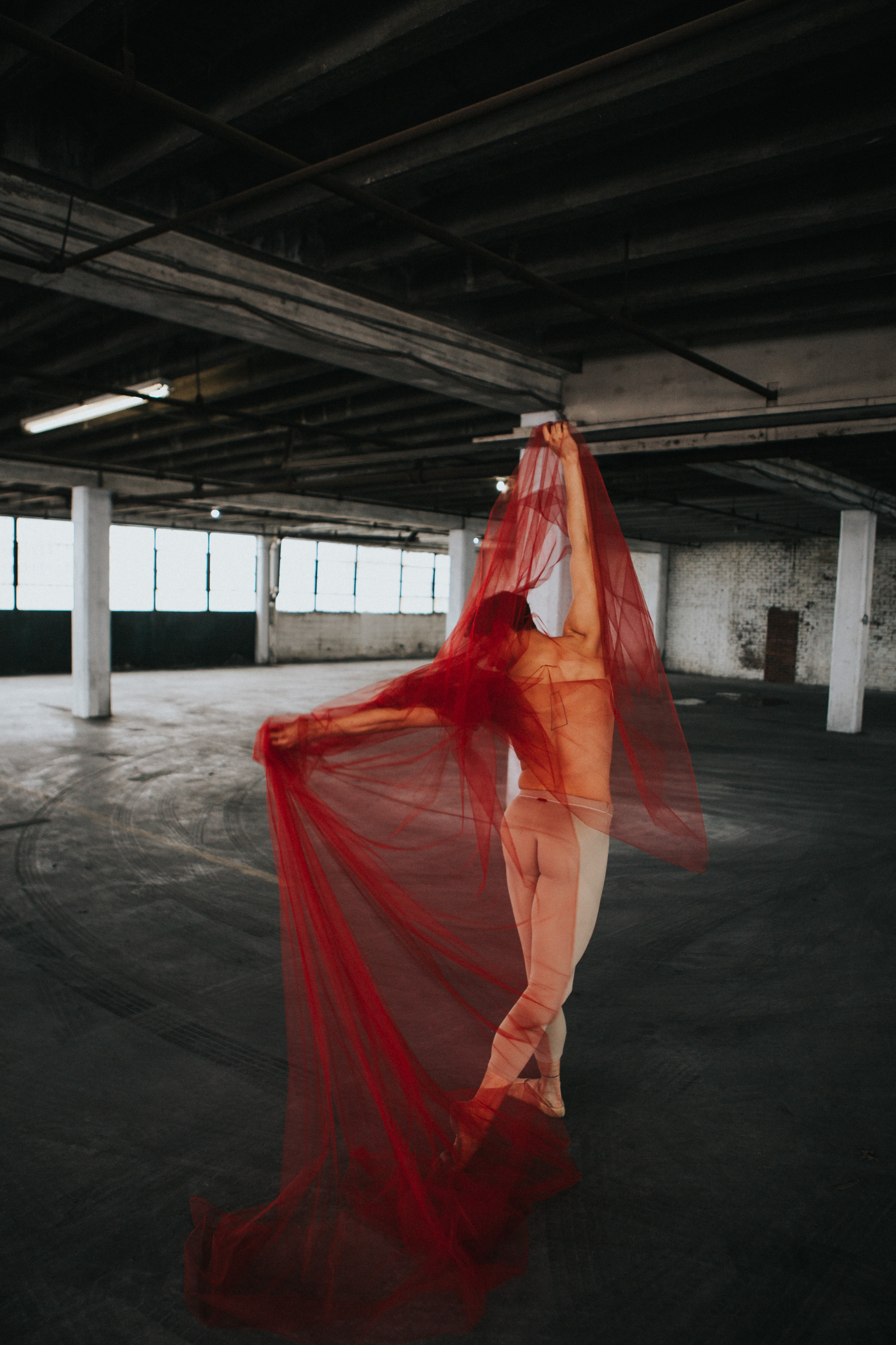 woman wearing red dress dancing on vehicle parking area