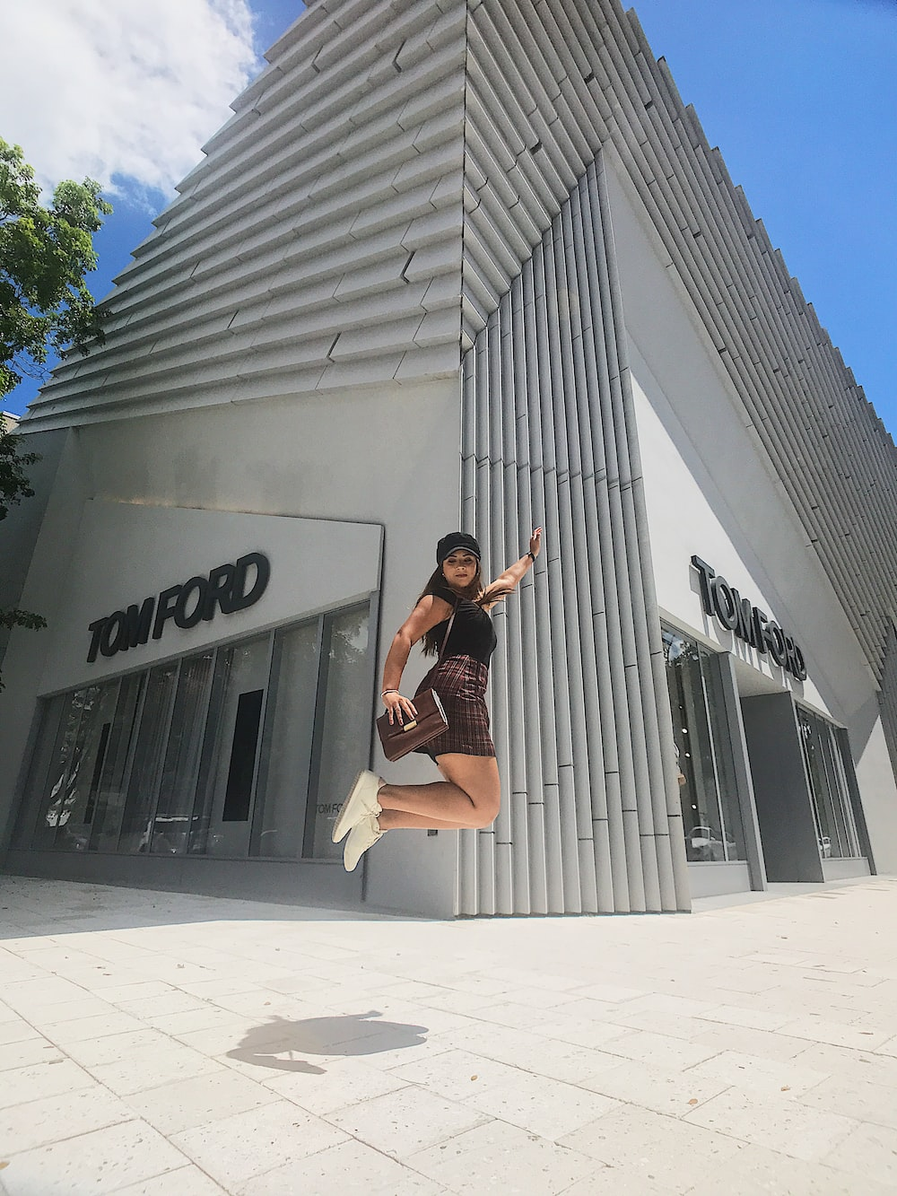 jumping woman near Tom Ford building during daytime