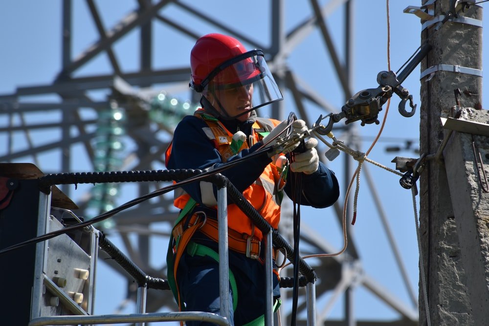 shallow focus photo of man fixing steel cable