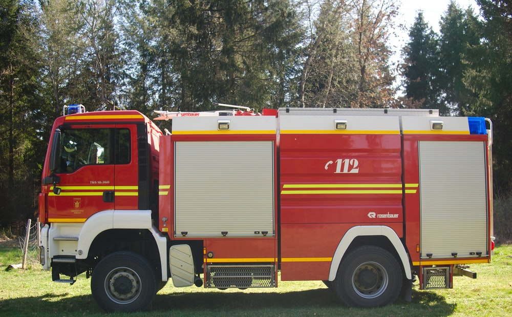red firetruck near green trees during daytime
