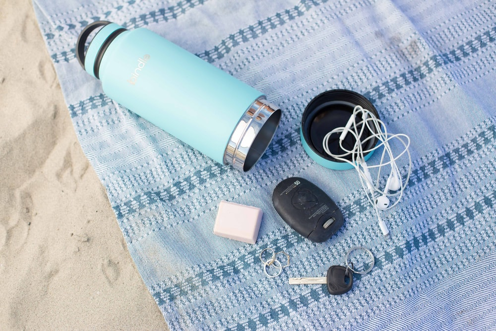 teal stainless steel travel mug with fob, key and earbuds on blue textile