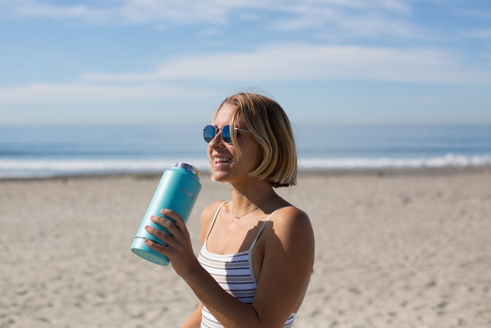 woman in white and brown pinstriped sleeveless top holding blue tumbler while smiling and standing near seashore at daytime